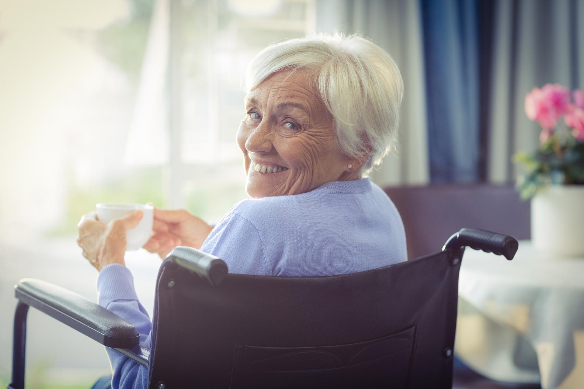 happy senior woman on wheelchair holding a cup of tea at home - Die Betreuung in häuslicher Gemeinschaft ist ein zukunftsfähiges, transparentes und absolut sicheres Modell